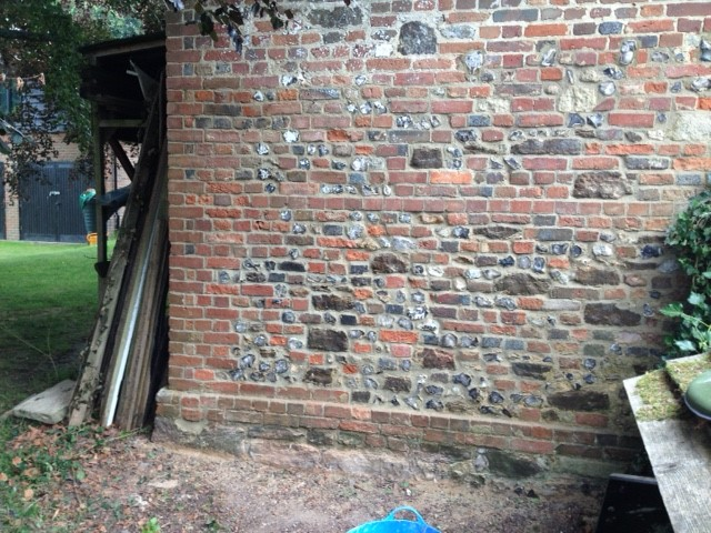 Repaired lime, brick and flint wall