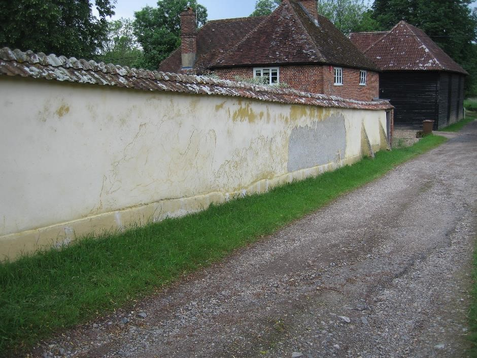 Flaking and leaning cob wall